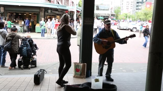 footage near pike place market as street performers play the violin in seattle wa on may 18 2017 shots full shot of two performers playing the violin... - pike place market stock videos and b-roll footage