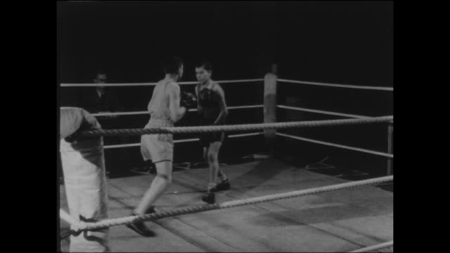 footage of a 1950s boys boxing match action between the boys before the end of the round they go back to the ring and their scores are marked on a... - gesellschaftsgeschichte stock-videos und b-roll-filmmaterial