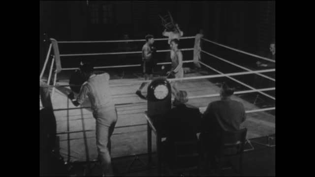 footage of a 1950s boys boxing match end of the first round the boys go back to their corners to the cheers of the crowd - gesellschaftsgeschichte stock-videos und b-roll-filmmaterial