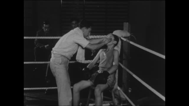 footage of a 1950s boys boxing match the boy's trainer wipes him down and offers advice on how to win the fight - gesellschaftsgeschichte stock-videos und b-roll-filmmaterial