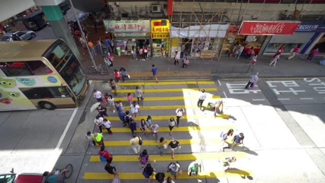 stockvideo's en b-roll-footage met 4k beelden van een drukke crosswalk mongkok gebied, mong kok is een wijk in het district yau tsim mong, op het westelijk deel van het schiereiland kowloon in hong kong - hong kong