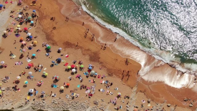 stockvideo's en b-roll-footage met 4k-beelden van een druk strand in de zomer - zonwering