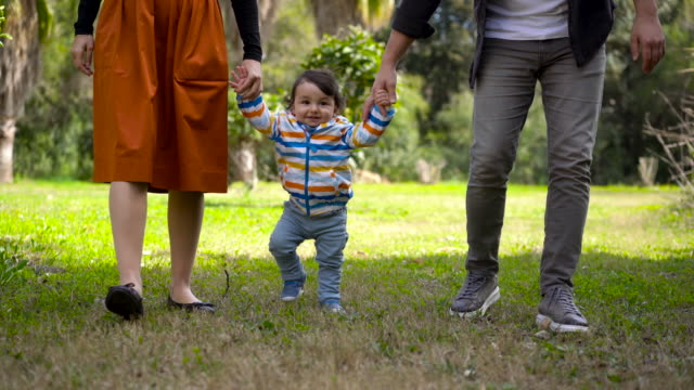 4k footage of a cute little baby boy learning to walk with father and mother at park - turkish ethnicity stock videos & royalty-free footage