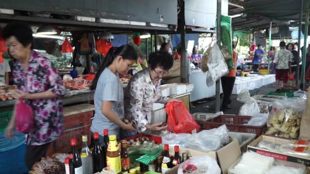 Footage of a food market in Kuala Lumpur Malaysia on September 29 2015 Shots wide shot of food market under tarps as customers walk by footage of...