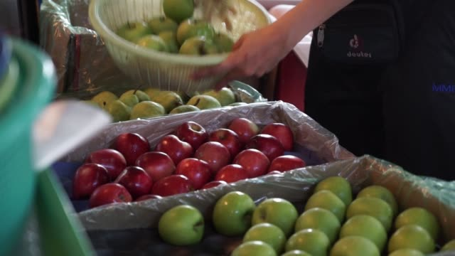 Footage of a food market in Kuala Lumpur Malaysia on September 29 2015 Shots wide shot of table of produce as customer interacts with worker tighter...