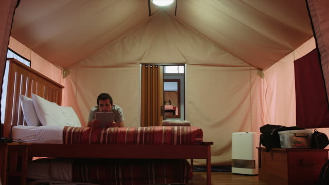 4K footage of a man reading in a 'glamping' tent, Victoria, Australia