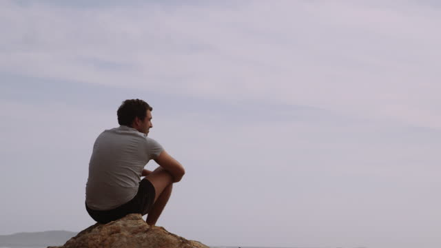 4k footage of a man seating on a rock in wilson promontory - ein mann allein stock-videos und b-roll-filmmaterial