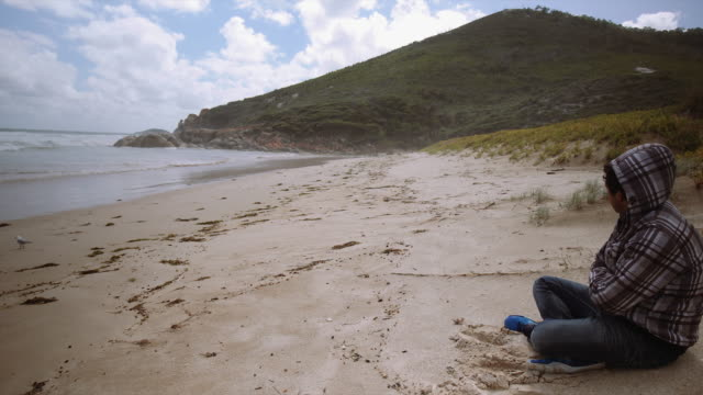 4K footage of a man seating on the beach, Wilson Promontory, Victoria, Australia