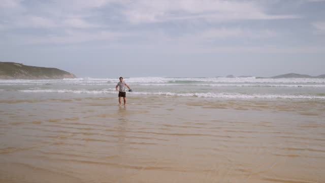 4k footage of a man walking on the beach and having fun, wilson promontory - one mid adult man only stock videos & royalty-free footage