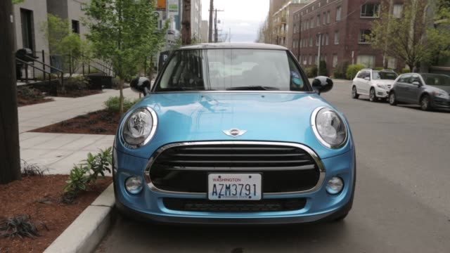 Footage of a MINI 2door electric vehicle part of the ReachNow carshare program parked in Seattle Washington US on Monday April 11 2016 Shots wide...