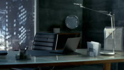 Footage of a Modern Office with Leather Chair, Wood and Glass Table with Laptop on It. Workspace is Made with Dark Overtones, Megapolis is Seen out of the Window.