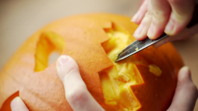 footage of a person carving out the teeth of a halloween pumpkin - intagliare video stock e b–roll
