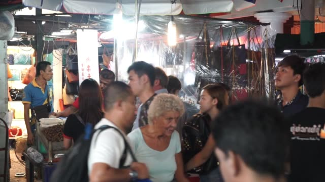 Footage of a populated market at night in Kuala Lumpur Malaysia on September 29 2015 Shots shot of jewelry stand as customer looks at what is for...
