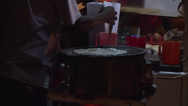 footage of a roadside small business owner who relies on solar power to light his roadside food kiosk. grid power is expensive for and many times not... - kampala stock-videos und b-roll-filmmaterial