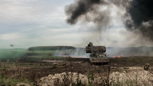 footage of a warrior armoured vehicle powering through an explosion as the british army demonstrated the latest technology in salisbury plain... - army stock-videos und b-roll-filmmaterial