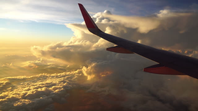 4K Footage of Airplane flying over the fantastic cloud and sky at the sunset time, Travel and transportation concept