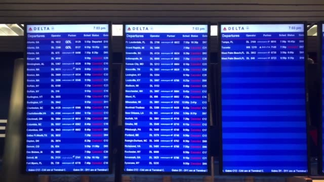 Footage of an empty Delta Airlines terminal at LaGuardia and of arrival and departure screens displaying flight cancellations due to Winter Storm...