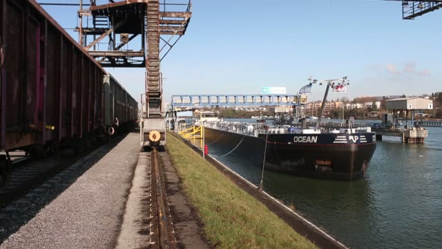 Footage of an oil tanker barge and the Caland Canal in Rotterdam Netherlands on Sunday Feb 14 2016 Shots wide pan right of hose filling oil into...