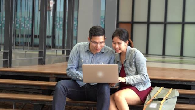 vídeos de stock, filmes e b-roll de filmagens de 4k de colega amante asiática em traje casual trabalhando pelo laptop no ambiente de trabalho moderno ao ar livre enquanto o seu sucesso vindo e parabéns juntos, negócios e conceito freelance - coworking space