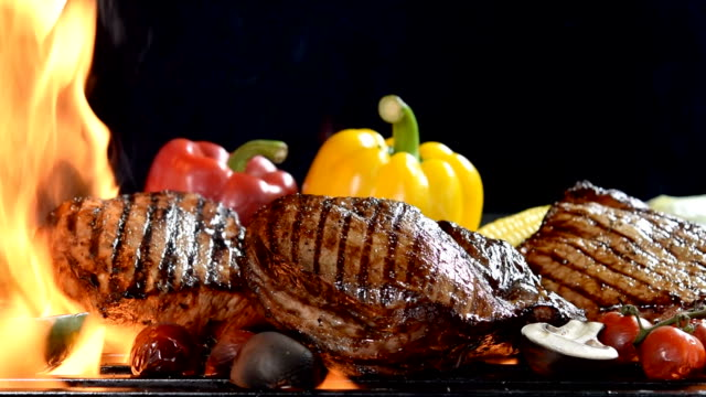 Footage of assorted grilled meat with vegetable on the flaming grill