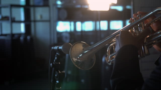 4k footage of back side musician playing button and pushing on trumpet with microphone over the spot light in music room background.planing from left to right - brass instrument stock videos & royalty-free footage