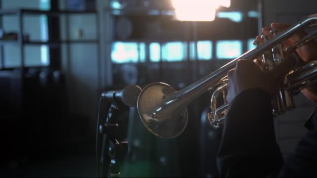 4 K film av baksidan musiker spela knappen och trycka på trumpet med mikrofon över plats ljus i musik rum background.planing från vänster till höger