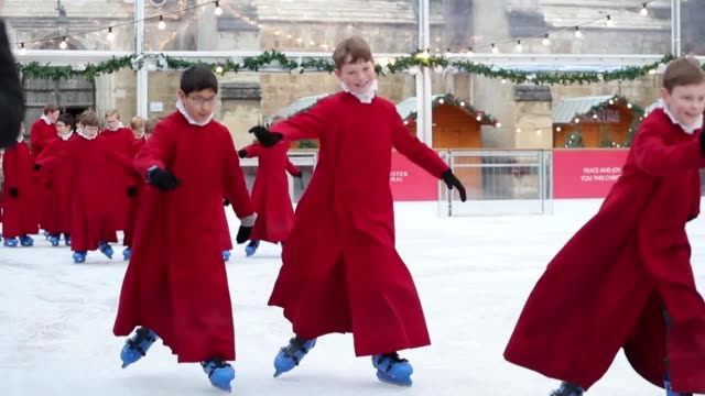 footage of boy choristers going ice skating on winchester cathedral's ice rink the choristers bright red gowns surrounded by the white of the ice... - chorsänger stock-videos und b-roll-filmmaterial