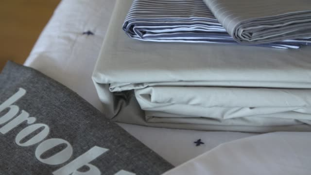 footage of brooklinen fabrics and sheets on display at the brooklinen offices in brooklyn, ny on april 19, 2017. shots: several folded sheets sitting... - folded stock videos & royalty-free footage