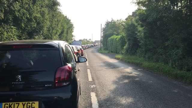 Footage of cars queuing and of a man running with a chair to reach the Glastonbury Festival at Worthy Farm in Pilton