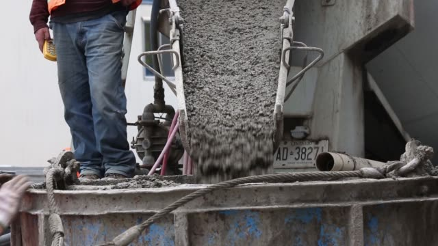 stockvideo's en b-roll-footage met footage of cement being mixed for use with condo under construction in toronto ontario canada in may 26 2017 shots worker sits in building as workers... - cement