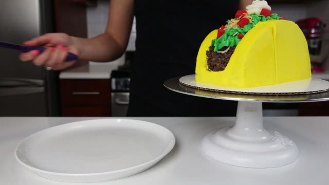 Footage of Chelsey White a selftaught baker who launched chelsweets and built a following on Instagram of 264k building a taco cake at her apartment...