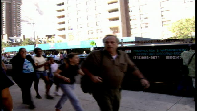 footage of crowds of people watching the aftermath of one of the world trade center towers collapse and running away from the massive cloud of dust... - 2001 bildbanksvideor och videomaterial från bakom kulisserna