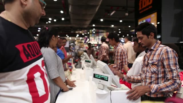 Footage of customers buying items at checkout in a Big Bazaar in Mumbai India on April 17 2017 Shots customers wait in line to checkout / employee...