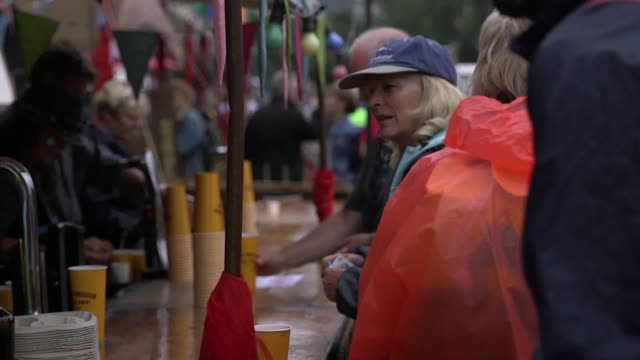 Footage of Day 4 at the Glastonbury festival People eating food and buying drinks footage of a chained man performing guests covered with raincoats...