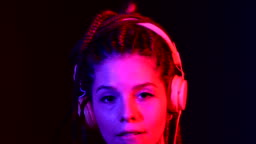 Footage of Dj woman with tree braids, dancing with headphones. With blue and red color lights.