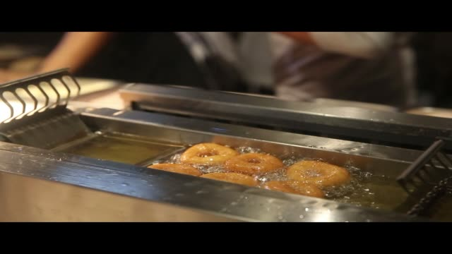 footage of donuts being fried at a donut stand in chelsea market in the chelsea neighborhood of manhattan, ny on may 3, 2017. shots: several donuts... - chelsea new york stock videos & royalty-free footage