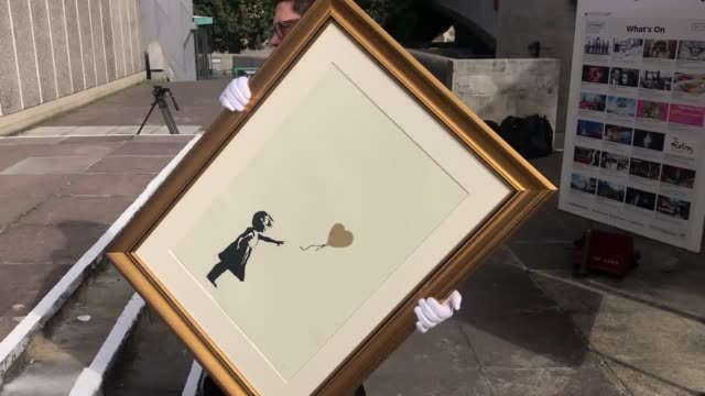 vídeos y material grabado en eventos de stock de footage of employees from the auction house christie's with different versions of 'girl with balloon' by anonymous street artist banksy near one of... - subasta