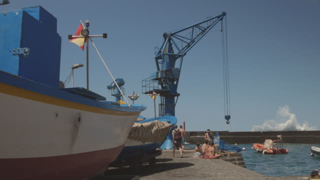 4k footage of fishing boats, with the spanish flag, and people at puerto de la cruz, tenerife - 大西洋諸島点の映像素材/bロール