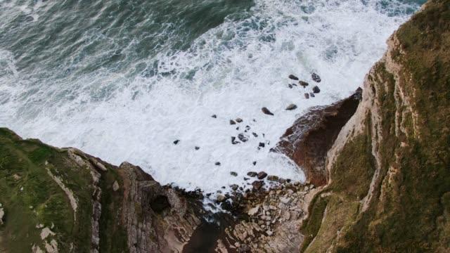 vídeos y material grabado en eventos de stock de imágenes 4k de altos acantilados verdes y olas chocando - bahía