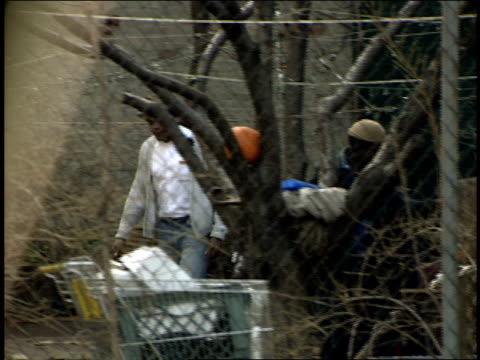 vídeos y material grabado en eventos de stock de footage of homeless behind chainlink fence - terrenos a construir