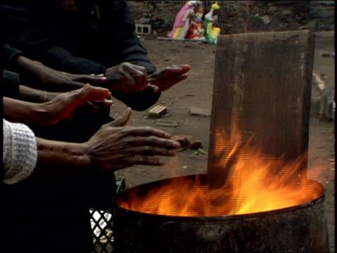 vídeos y material grabado en eventos de stock de footage of homeless warming hands by trash fire - terrenos a construir