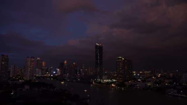 vídeos de stock, filmes e b-roll de 4 k filmagens de relâmpago com nuvens de tempestade à noite sobre a banguecoque cityscape rio lado, tailândia, natureza e paisagem urbana conceito - overcast