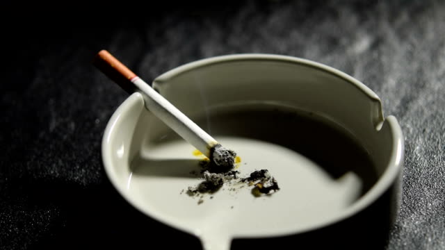 Footage of lit and smoking cigarette burning on an ashtray