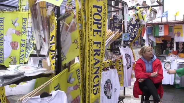 footage of merchandise on sale in dublin ahead of the arrival of pope francis also vox pops with visitors to the city - ローマ法王点の映像素材/bロール