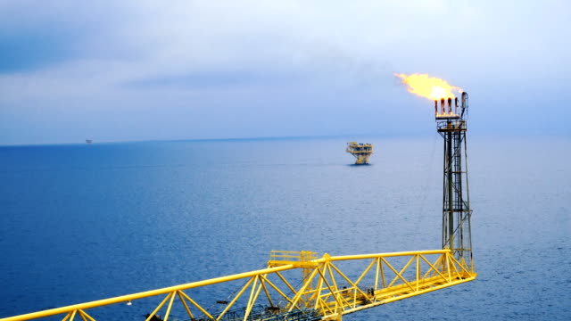 footage of oil and gas platform with flare burning bridge with sun rise and beautiful clouds in the morning for oil and gas industry concept. - burning stock videos & royalty-free footage