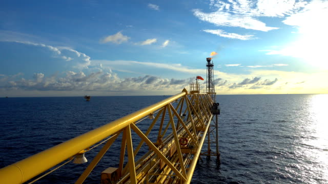 footage of oil and gas platform with flare burning bridge with sun rise and beautiful clouds in the morning for oil and gas industry concept. - piattaforma offshore video stock e b–roll