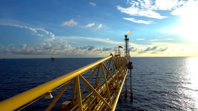 vídeos de stock, filmes e b-roll de imagens de plataforma de petróleo e gás com queima de ponte com o nascer do sol e nuvens bonitas de manhã para o conceito de indústria de petróleo e gás de flare. - plataforma marítima