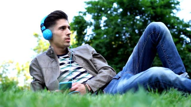 音楽を聴くと、公園の芝生の上で休んでいる一人の男の映像