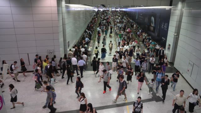 4k footage of passengers walking in crowded in rush hour at interexchange between hongkong airport and subway - hong kong international airport stock videos & royalty-free footage