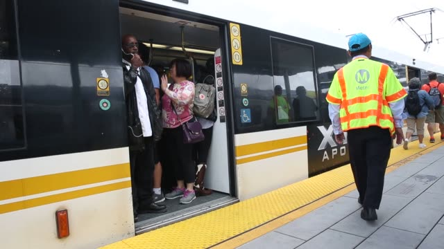 Footage of pedestrians boarding the Metro Expo Line light train at a rail station in Santa Monica California US on Friday May 20 2016 Shots wide...